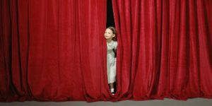 Girl (7-9) looking out from behind stage curtain